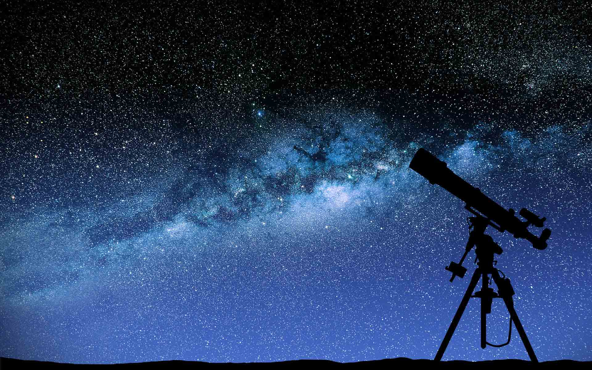 There is a telescope in front of the night sky filled with stars.